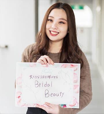 「大切な1日を輝かせるBridal Beauty」のパネルを持つ生徒